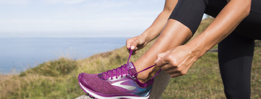 Female runner stops to tie shoelace