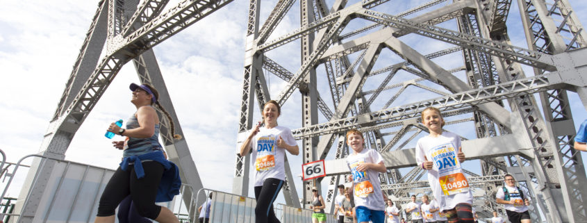 woman and two boys running across story bridge