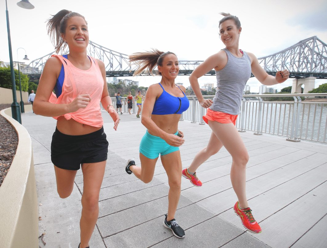 three girls running along boardwalk with story bridge in background preparing for bridge to brisbane day 2017
