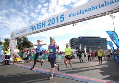 people cross the bridge to brisbane finish line in bowen hills